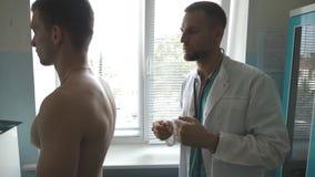 Médico que verificam para trás e caixa do indivíduo em seu escritório no hospital Doutor que examina o paciente masculino novo co filme