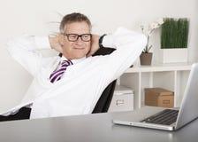 Médico relajado Smiling While Watching en el ordenador portátil Foto de archivo