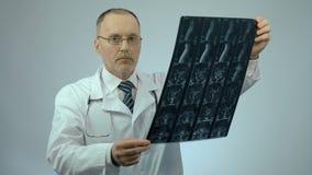 Médico sério que verifica a imagem ferida da exploração da espinha, olhando a câmera filme