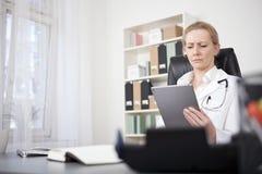 Médico sério Reading em sua tabuleta imagens de stock