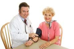 Médico sênior - tomando a pressão sanguínea Fotografia de Stock