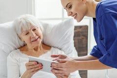 Médico saliente que ayuda a utilizar la tableta Fotografía de archivo