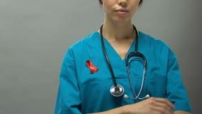 Médico serio de la mujer con campaña de concienciación favorable de las AYUDAS de la cinta roja almacen de video