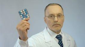 Médico serio que sostiene píldoras medicación eficaz disponible, de recomendación almacen de video