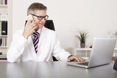 Médico Using Mobile Phone y ordenador portátil Fotografía de archivo