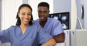 Médicos afroamericanos que se sientan junto por el ordenador Fotos de archivo libres de regalías
