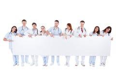 Médicos amistosos que sostienen una bandera en blanco Imagen de archivo libre de regalías