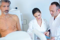 Médicos con el hombre envejecido medio desnudo imagen de archivo libre de regalías