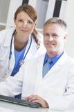 Médicos de hospital hembra-varón que usan el ordenador imagen de archivo