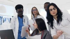 Médicos multinacionais novos que têm a reunião, usando o portátil e os documentos de papel durante o dia do trabalho no hospital video estoque