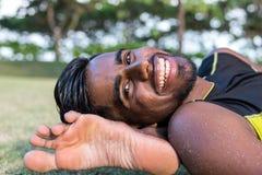 Médicos novos do homem da ioga que fazem a ioga na natureza Homem indiano asiático dos iogues na grama no parque Ilha de Bali Foto de Stock Royalty Free