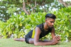 Médicos novos do homem da ioga que fazem a ioga na natureza Homem indiano asiático dos iogues na grama no parque Ilha de Bali Fotografia de Stock