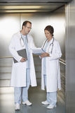 Médicos que discuten la carta en elevador del hospital Fotografía de archivo libre de regalías