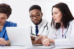 Médicos que têm a discussão usando o portátil na sala de reunião fotografia de stock
