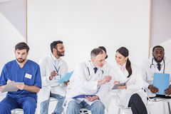 Médicos salientes que arreglan conferencias en clínica foto de archivo libre de regalías