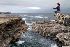Méditation au bord d'une falaise Photos libres de droits