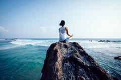 méditation de femme à la roche de bord de la mer photographie stock