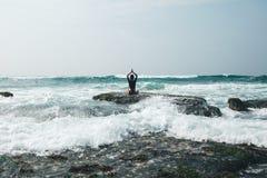 Méditation de femme au bord croal de falaise de bord de la mer photographie stock
