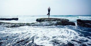 Méditation de femme au bord croal de falaise de bord de la mer image stock