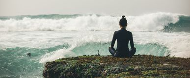 Méditation de femme de yoga au bord de falaise de bord de la mer photos stock