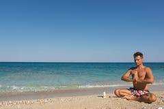 Méditation de matin, homme adulte sur la plage Images stock