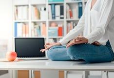 Méditation de pratique de femme sur un bureau photographie stock