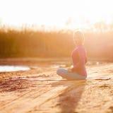 Méditation de yoga, femme sur le coucher du soleil Photographie stock libre de droits