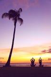Méditation de yoga - silhouettes des personnes au coucher du soleil Images stock