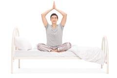 Méditer de jeune homme posé sur un lit Images stock