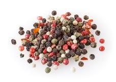 Mélangé de différents grains de poivre aimables d'isolement sur le blanc photos stock
