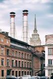 Mélange de deux tuyaux et bâtiments de différentes périodes contre le ciel bleu Vieux bâtiment industriel de l'usine du rouge Photographie stock