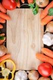 Mélange de légumes frais autour de planche à découper en bois Photographie stock libre de droits