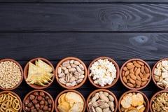 Mélange des bretzels, des biscuits, des pommes chips, des écrous et des nachos de casse-croûte photo stock