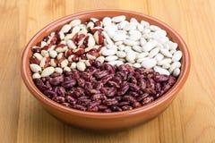 Mélange des haricots - rouges et blancs dans un plat sur une table en bois Photo libre de droits