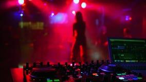 Mélangeur de contrôleur du DJ dans la boîte de nuit avec la silhouette brouillée du chanteur de fille de danse banque de vidéos