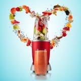 Mélangeur de Smoothie avec des ingrédients de vol de boissons et de fruit au coeur Image stock