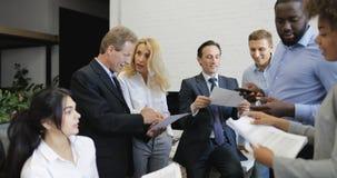 Mélangez le secrétaire de course présentant à des gens d'affaires des rapports d'équipe aux résultats réussis, hommes d'affaires  banque de vidéos