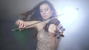 Mélodie soloe, interprète musical avec le violon dans des mains au considérant dans le projecteur lumineux banque de vidéos