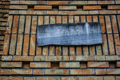 Mémorial antique avec des écritures roumaines, mur de briques orange Photos stock