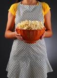 Ménagère retenant un bol de maïs éclaté Photos stock