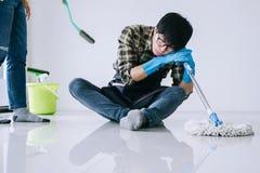 Ménage de mari et concept de nettoyage, homme fatigué dans la bande de frottement bleue photo stock