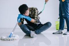 Ménage de mari et concept de nettoyage, homme fatigué dans la bande de frottement bleue photographie stock libre de droits