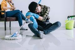 Ménage de mari et concept de nettoyage, homme fatigué dans les gants en caoutchouc bleus essuyant la poussière utilisant le balai images stock
