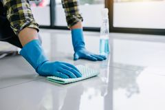 Ménage de mari et concept de nettoyage, jeune homme heureux dans les gants en caoutchouc bleus essuyant la poussière utilisant un photos stock