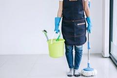 Ménage et concept de nettoyage, jeune femme heureuse dans la bande de frottement bleue photographie stock