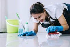 Ménage et concept de nettoyage, jeune femme heureuse dans la bande de frottement bleue photographie stock libre de droits