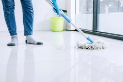 Ménage et concept de nettoyage, jeune femme heureuse dans la bande de frottement bleue image stock