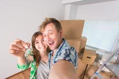 Ménages mariés drôles avec des boîtes et tenir des clés plates Photographie stock libre de droits
