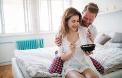Ménages mariés heureux étant romantiques dans le lit partageant la céréale Photos stock