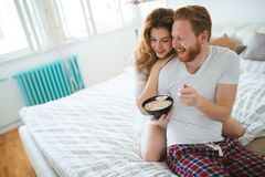 Ménages mariés heureux étant romantiques dans le lit partageant la céréale Photographie stock